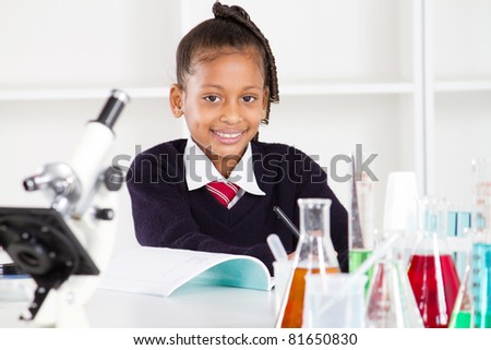 happy female elementary school pupil in science class - stock photo