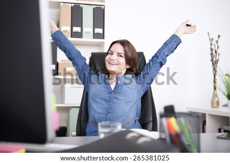Happy Female Executive Sitting on her Chair at the Office While Stretching her Arms and Looking at the Camera. - stock photo