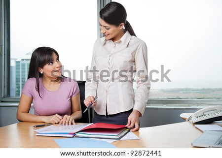 Happy female executives discussing business reports in office - stock photo