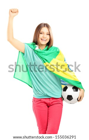 Happy female fan with brazilian flag holding a soccer ball isolated on white background