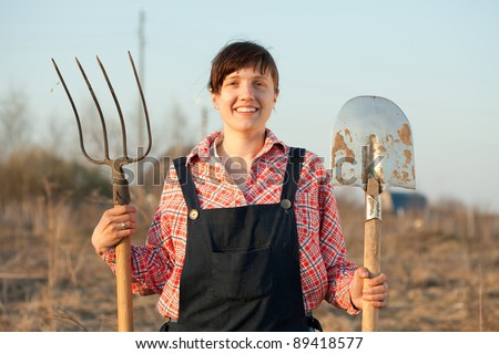 Happy female farmer  with spade and pitchfork in field - stock photo