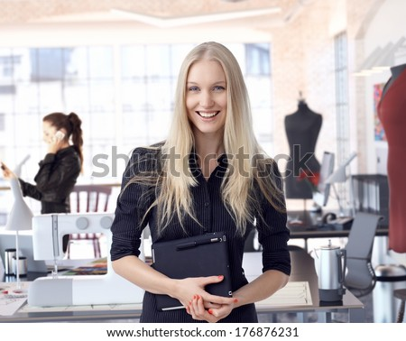 Happy female fashion designer entrepreneur at creative studio leading small business. Businesswoman holding tablet, smiling. - stock photo