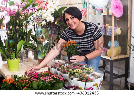 Happy female florist arranging a kalanchoe calandiva in the gardening department