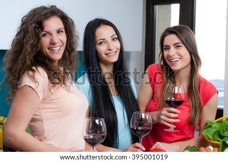 Happy female friends enjoying in the kitchen, spending great time. They are drinking wine and enjoying while cooking together. - stock photo