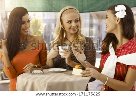 Happy female friends having cake and coffee, chatting at outdoor cafe. - stock photo