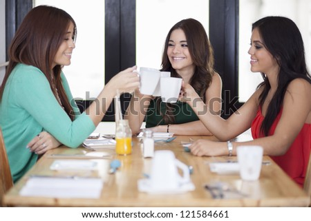 Happy female friends having fun and making a toast with coffee