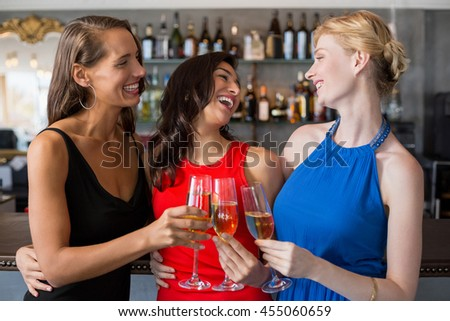 Happy female friends holding glass of champagne flute in restaurant