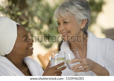 Happy female friends in bathrobe toasting - stock photo