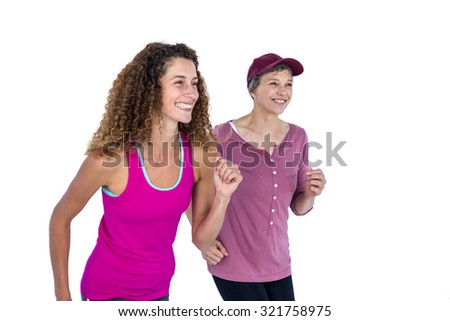 Happy female friends jogging against white background - stock photo