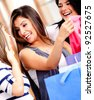 Happy female friends shopping at a retail store - stock photo