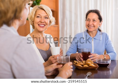 Happy female friends talking during tea drinking at home. Focus on blonde - stock photo