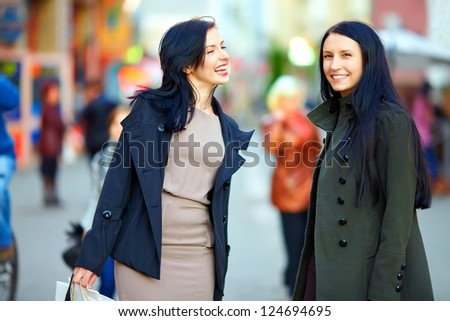 happy female friends walking the crowded city street