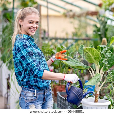 happy female gardener working in greenhouse