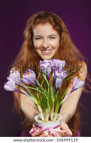 Happy female giving flowers crocuses. Shallow deep of field. Focus on flowers. - stock photo