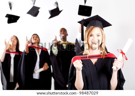 happy female graduate at graduation with classmates throwing caps in background - stock photo