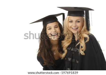 Happy female graduates hugging, wearing square academic cap, smiling. - stock photo