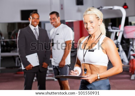 happy female gym trainer portrait with colleagues in background - stock photo
