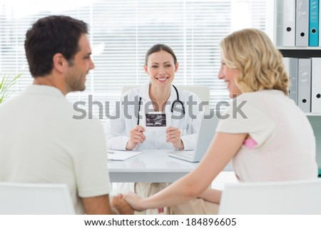 Happy female gynaecologist looking at expectant couple in clinic - stock photo