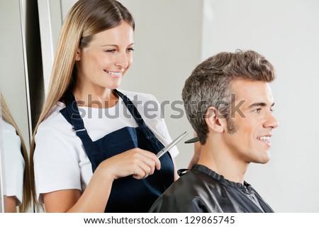 Happy female hairdresser cutting customer's hair at salon - stock photo