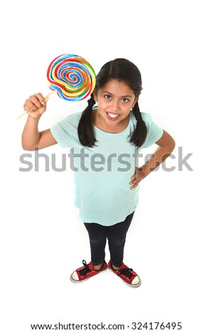 happy female hispanic child holding big lollipop candy in cheerful face expression in sugar addiction and kid love for sweet concept isolated on white background - stock photo