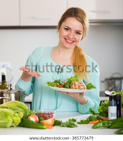 Happy female holding plate with salad and cheese in kitchen