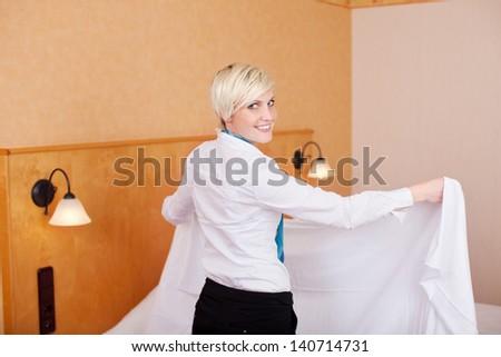 Happy female housekeeper making bed in hotel room - stock photo