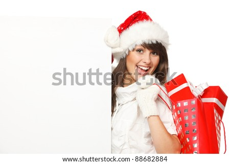 Happy female in Santa hat holding Xmas gifts and blank billboard, isolated on white background - stock photo