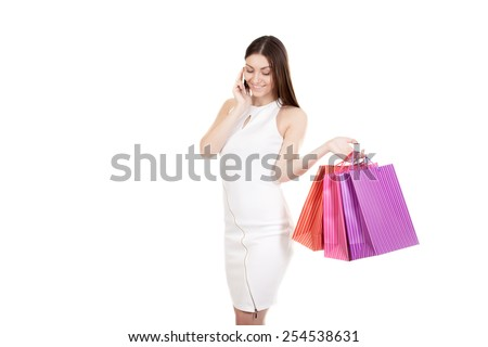 Happy female in white dress shopping, holding colored paper bags in her hand, talking on the cell phone, smartphone, making call. Isolated on white background, copy space
