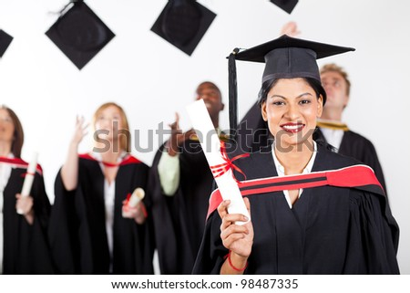 happy female indian graduate at graduation with classmates throwing caps - stock photo