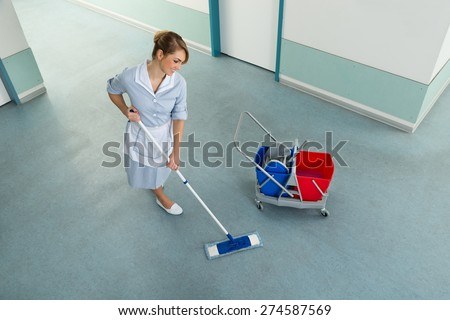 Happy Female Janitor With Mop And Cleaning Equipment On Floor - stock photo