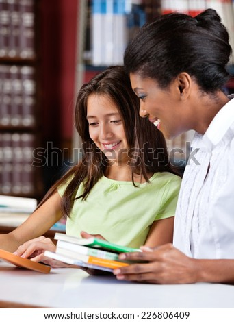 Happy female librarian and schoolgirl looking together at book in library - stock photo