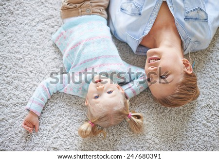 Happy female looking at her daughter while both lying on the floor - stock photo