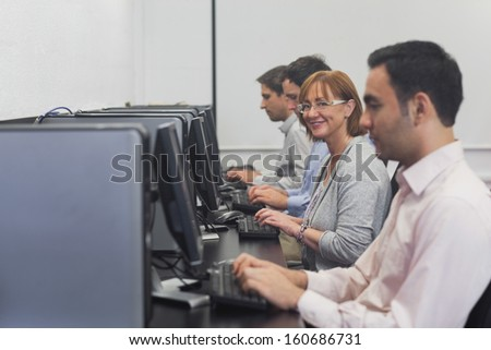 Happy female mature student sitting in computer class smiling at camera - stock photo