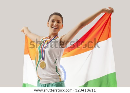 Happy female medalist celebrating victory with Indian flag isolated over gray background