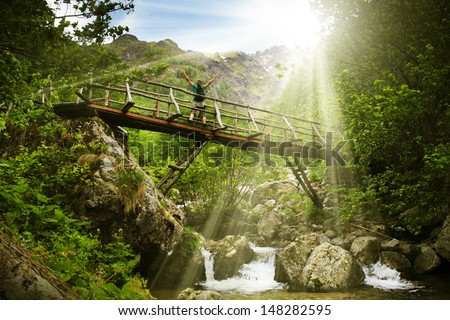 Happy female mountaineer standing on a wooden bridge over a mountain stream overflowing with excitement with the glory and beauty of the wild natural park - stock photo
