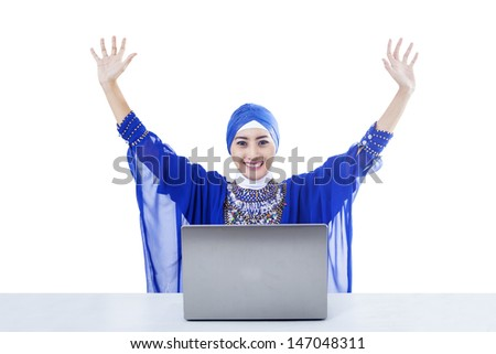 Happy female muslim in blue dress raised her arms with laptop on white - stock photo