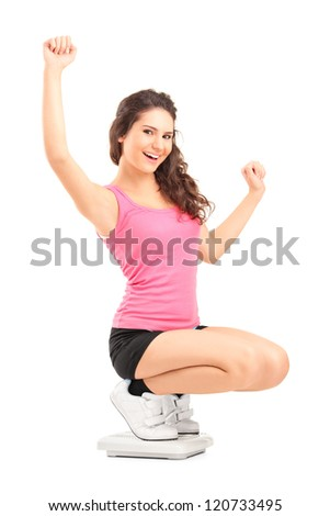 Happy female on a weight scale gesturing with her hands isolated on white background