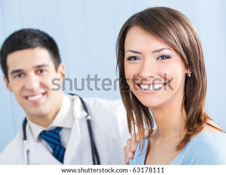 Happy female patient and doctor at office. Focus on woman. - stock photo