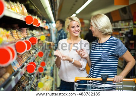 Happy female pensioner and her adult daughter choosing chilled sausages in supermarket