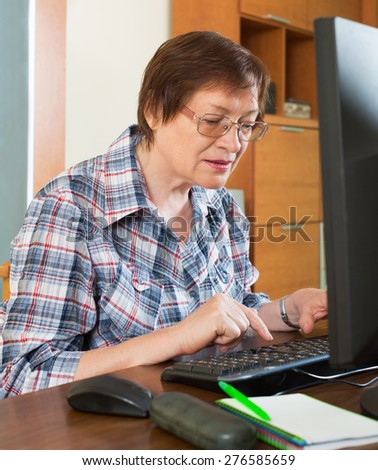 Happy female pensioner working with personal computer in office interior - stock photo