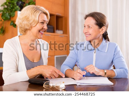 Happy female pensioners discussing contracts indoor.Focus on the woman on the left - stock photo