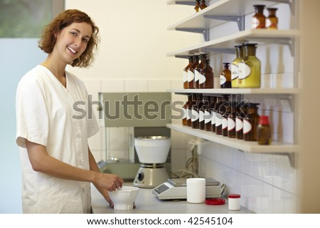 Happy female pharmacist preparing medication with mortar - stock photo
