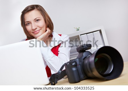 Happy female photographer in studio with camera and laptop computer - stock photo