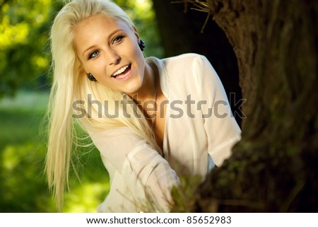 Happy female playing hide and seek. Hiding behind a big tree. - stock photo