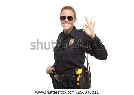 Happy female police officer gesturing OK sign against white background - stock photo