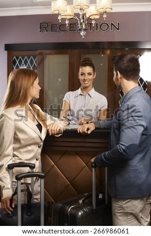 Happy female receptionist giving information to guests upon arrival. - stock photo