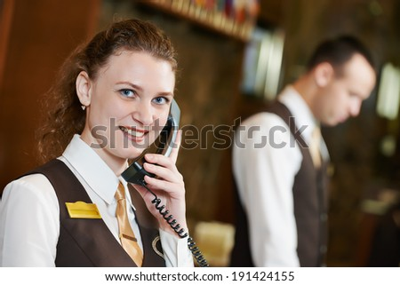 Happy female receptionist worker with phone standing at hotel counter - stock photo