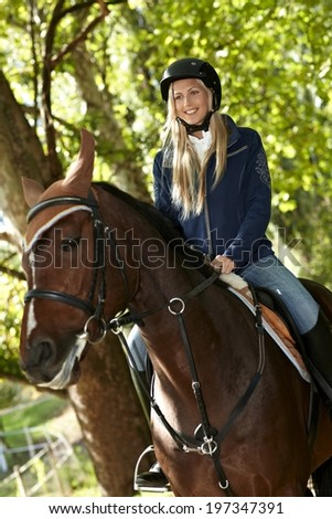 Happy female rider sitting on horseback, smiling. - stock photo