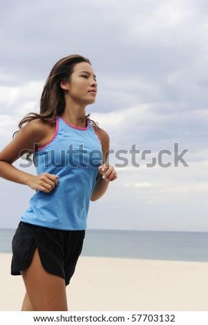 happy female runner running outdoors at the beach - stock photo