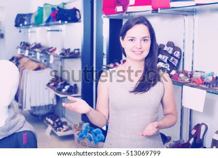 Happy female seller with dark hair working in shoes store